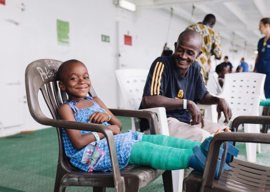 Mohammed, orthopedic patient, sitting with his father on Deck 7 after surgery.