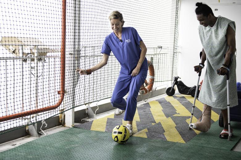 Cath Luyten op deck 7 met voetbal en patiënt van Mercy Ships