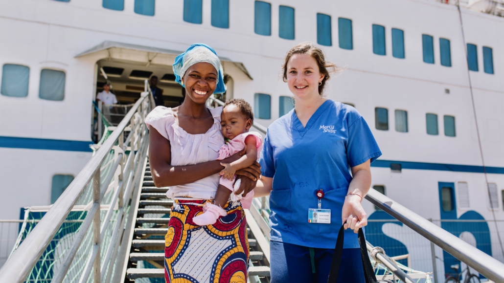 Aissata, cleft lip patient, after surgery coming down the gangway with her mother and Rachel Goodall, Ward Nurse.